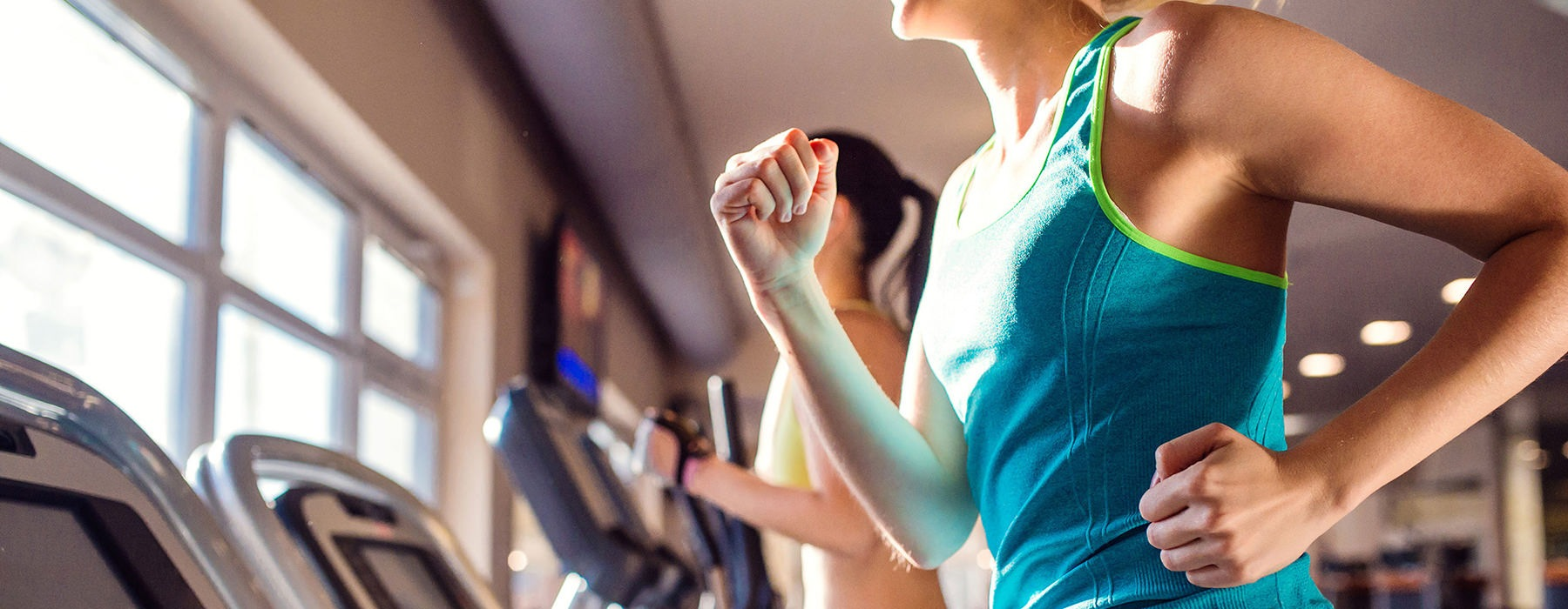 woman running on treadmill in fitness center