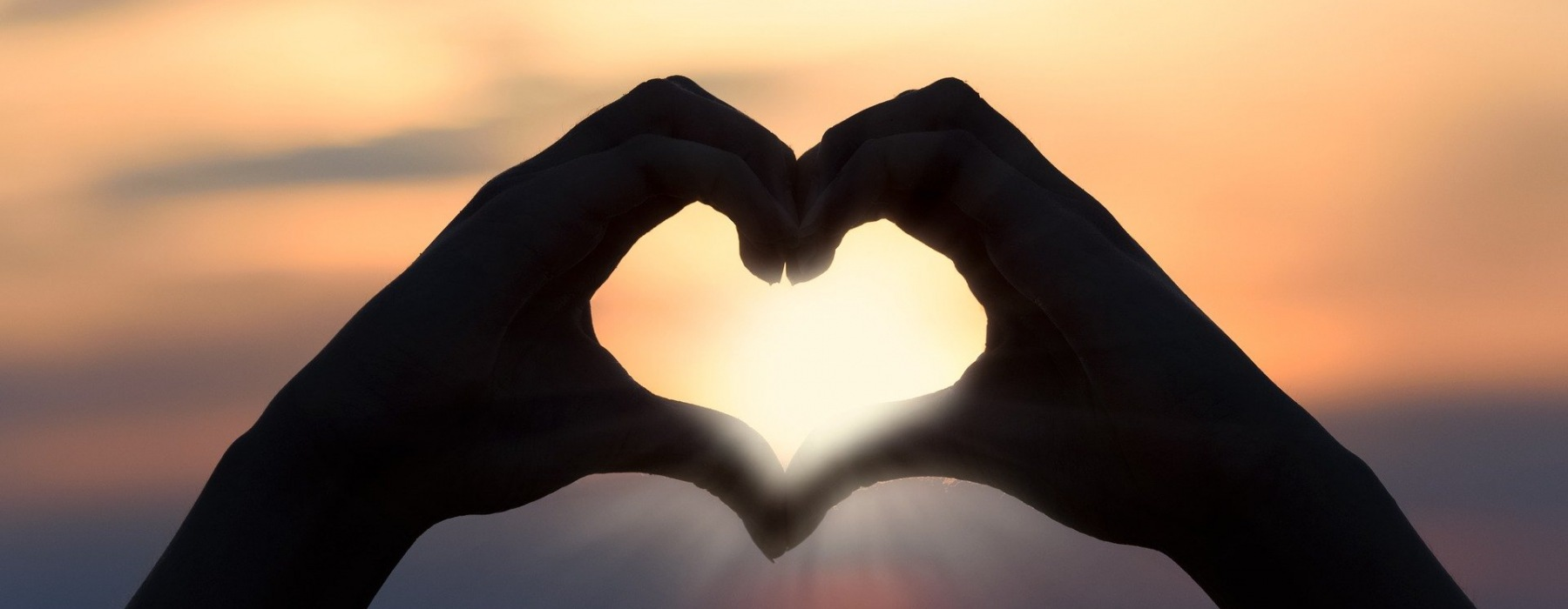 Hands shaping a heart silhouetted again the sunset