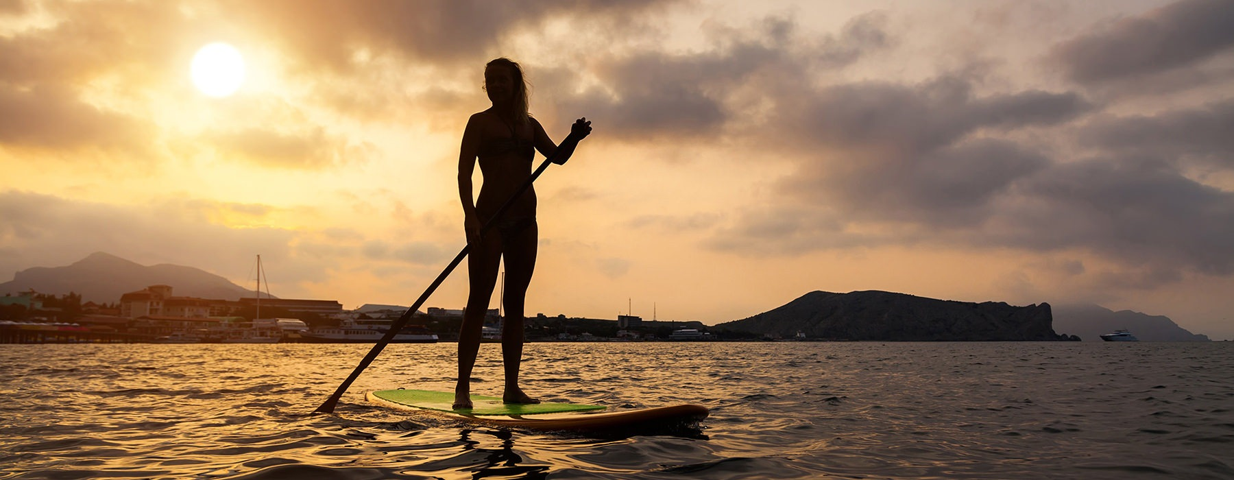 silhouette of woman on paddle board in the middle of the lake